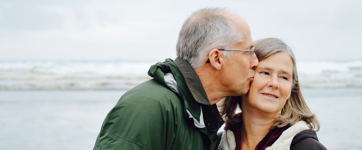Old man kisses old woman on the cheek