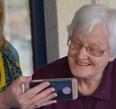 Carer holding phone for elderly woman