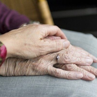 A person holding an elderly person's hand