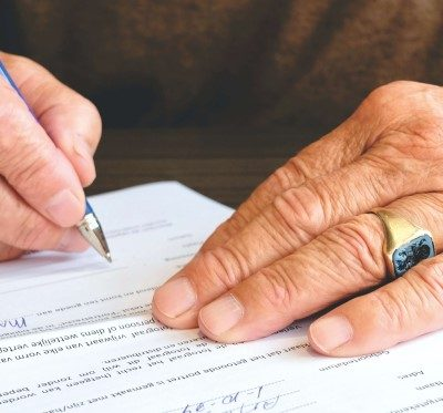 elderly person signing legal document