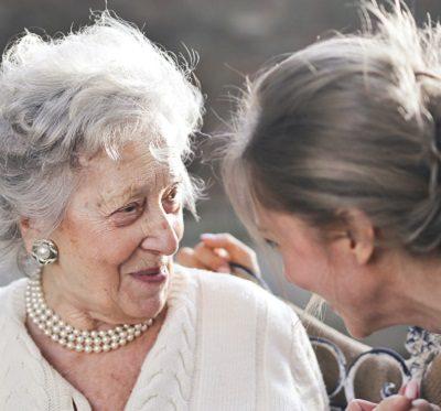 an elderly lady smiling at her carer