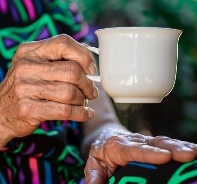 an elderly person drinking tea at home